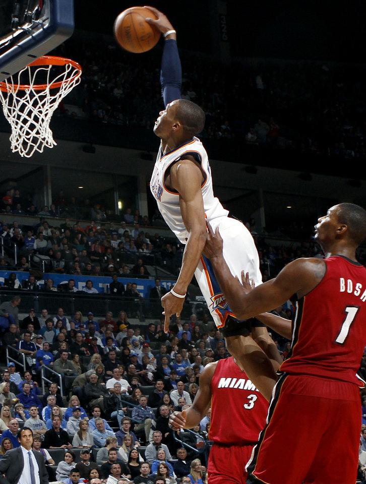 Photo - Oklahoma City's Russell Westbrook gets between Miami's Chris Bosh and Dwyane Wade to put in a slam dunk during their NBA basketball game at the OKC Arena in Oklahoma City on Thursday, Jan. 30, 2011. The Heat beat the Thunder 108-103. Photo by John Clanton, The Oklahoman
