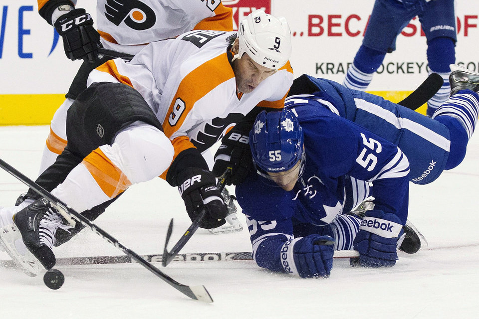 Photo - Toronto Maple Leafs' Korbinian Holzer (55) and Philadelphia Flyers' Mike Knuble (9) battle for the puck during the first period of their NHL hockey game, Monday, Feb. 11, 2013, in Toronto. (AP Photo/The Canadian Press, Chris Young)