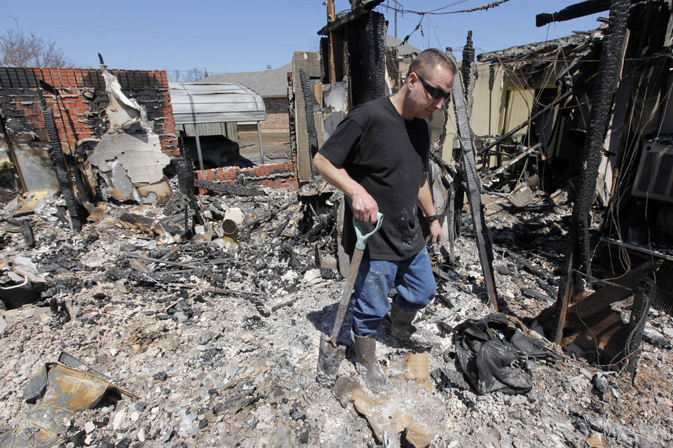 Photo - Todd Sewell walks through what is left of his home at 11533 Berkshire Ct. which was destroyed by fire, in Midwest City, Okla., Saturday, April 11, 2009. Wildfires struck the area on Thursday, April 9, 2009, destroying several homes. Photo by Nate Billings, The Oklahoman
