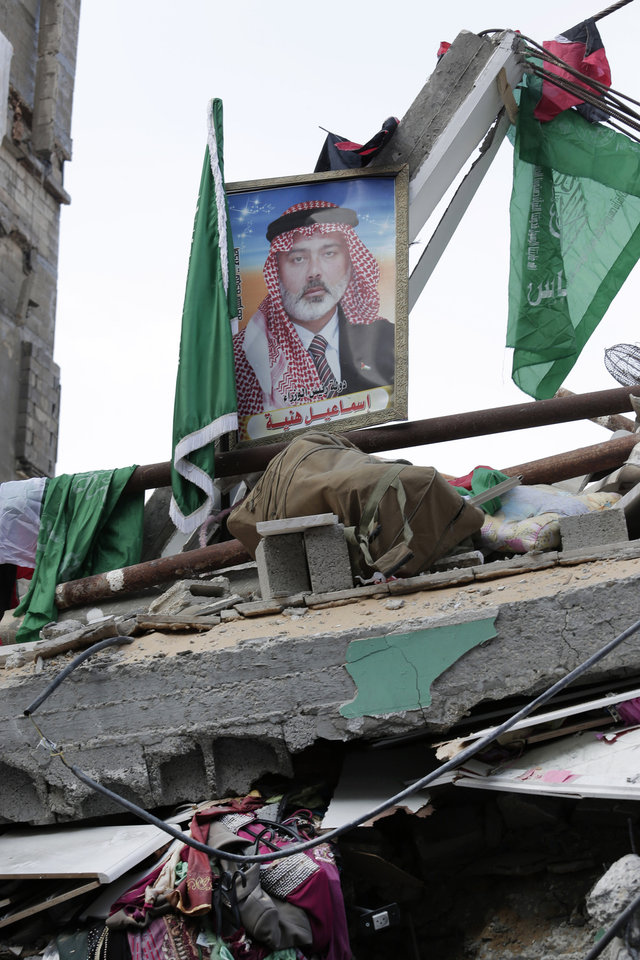 Photo - Palestinian and Islamic flags and a portrait of the top Hamas leader in Gaza, Ismail Haniyeh, are placed on the rubble of his house hit by a pre-dawn Israeli strike, in Gaza City, northern Gaza Strip, Tuesday, July 29, 2014. Early Tuesday, Israel warplanes struck a series of targets in Gaza City, including Haniyeh's house and government offices, while Gaza's border area with Israel was hit by heavy tank shelling. (AP Photo/Lefteris Pitarakis)