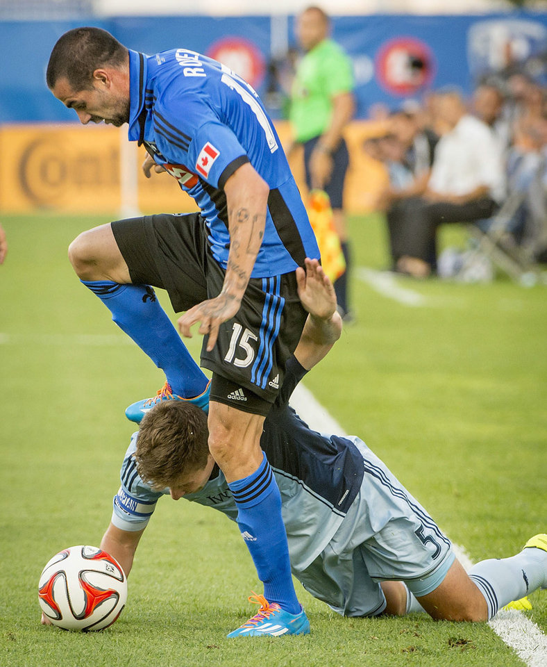 Photo - Montreal Impact's Andres Romero, top, battles with Sporting Kansas City's Matt Besler during the first half of a soccer game, Saturday, July 12, 2014 in Montreal. (AP Photo/The Canadian Press, Peter McCabe)