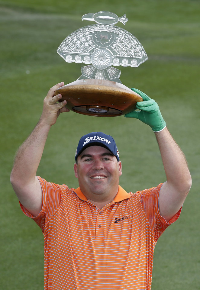 Photo - Kevin Stadler smiles as he poses for photographers with the championship trophy after winning the Phoenix Open golf tournament on Sunday, Feb. 2, 2014, in Scottsdale, Ariz. (AP Photo/Ross D. Franklin)