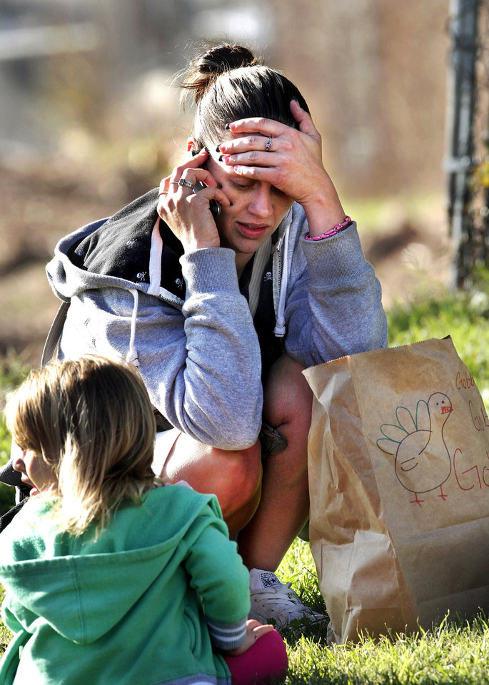 "Terra Wright, 29,  kneels on the ground and talks on the telephone after receiving her turkey and food.  Seated near her is three year-old daughter, Cherish.  Wright said she was very grateful for the food and remarked, "" without it, we wouldn't have had a Thanksgiving dinner.""  Wright has four children who live with her in Oklahoma City.  Jesus House distributed turkeys and grocery items Tuesday morning,  Nov. 19, 2012. Officials said they had 400 turkeys and food baskets to distribute and people were standing in line when their doors opened at 8 a.m. In less than two yours, all turkeys had been claimed. They will pass out 400 more turkeys and food baskets on Wednesday.  Photo by Jim Beckel, The Oklahoman"