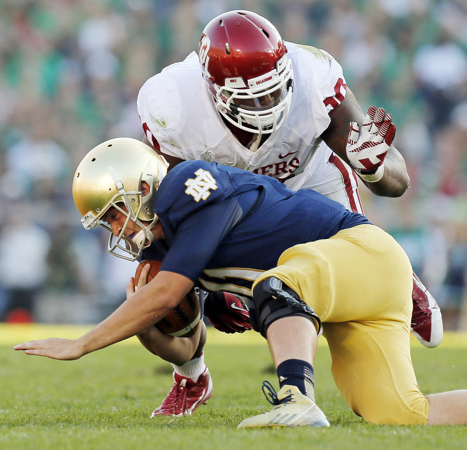 Photo - Oklahoma's Jordan Phillips (80) sacks Notre Dame's Tommy Rees (11) in the third quarter during a college football game between the University of Oklahoma Sooners and the Notre Dame Fighting Irish at Notre Dame Stadium in South Bend, Ind., Saturday, Sept. 28, 2013. OU won, 35-21. Photo by Nate Billings, The Oklahoman