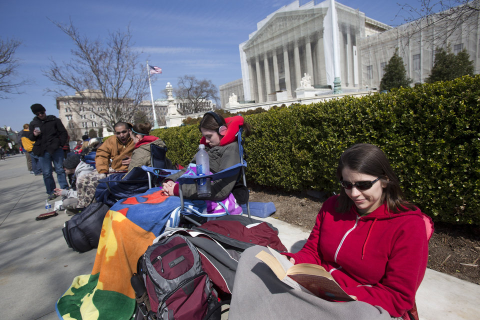 Photo - In this photo taken Saturday, March 23, 2013, Jessica Skrebes of Washington reads while waiting in line with others outside of the U.S. Supreme Court in Washington in anticipation of Tuesday's Supreme Court hearing on California's Proposition 8 ban on same-sex marriage, and Wednesday's Supreme Court hearing on the federal Defense of Marriage Act, which defines marriage as the union of a man and a woman. (AP Photo/Jacquelyn Martin)