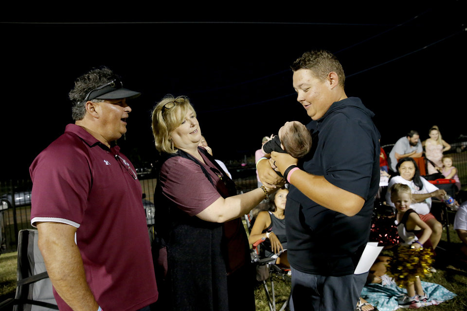Photo - Cashion assistant coach Cale Cochran visits his son Jaxon along with his parents, Chris and Kerry Cochran, during halftime of a high school football game between Cashion and Perry in Cashion, Okla., Friday, Sept. 4, 2020. Cochran's wife, Jacie, died July 2 shortly after giving birth to their son Jaxon. [Bryan Terry/The Oklahoman]