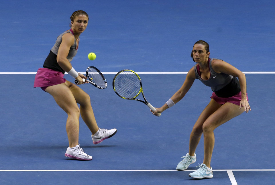 Photo - Italy's Sara Errani, left, and Roberta Vinci, right, play Russia's Ekaterina Makarova and Elena Vesnina in their women's doubles final at the Australian Open tennis championship in Melbourne, Australia, Friday, Jan. 24, 2014.(AP Photo/Aijaz Rahi)