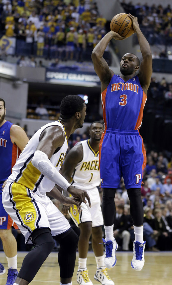 Photo - Detroit Pistons guard Rodney Stuckey, right, shoots over Indiana Pacers center Roy Hibbert in the first half of an NBA basketball game in Indianapolis, Monday, Dec. 16, 2013.  (AP Photo/Michael Conroy)
