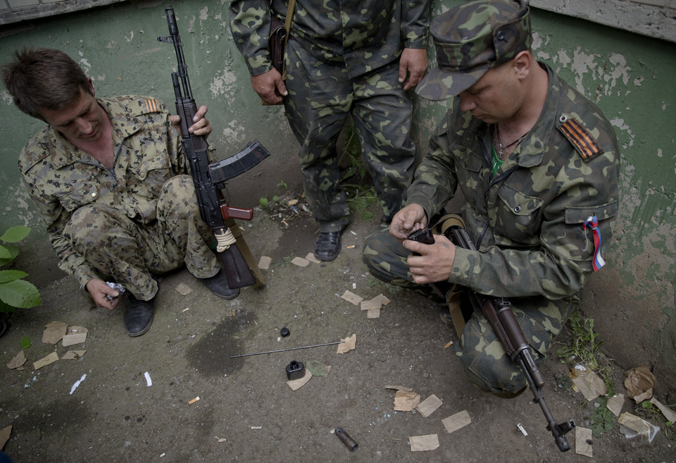 Photo - Pro-Russian rebels reload weapons during clashes with Ukrainian troops on the outskirts of Luhansk, Ukraine, Monday, June 2, 2014. Hundreds of pro-Russia insurgents attacked a border guard base in eastern Ukraine on Monday, with some firing rocket-propelled grenades from the roof of a nearby residential building. At least five rebels were killed when the guards returned fire, a spokesman for the border guard service said.(AP Photo/Vadim Ghirda)