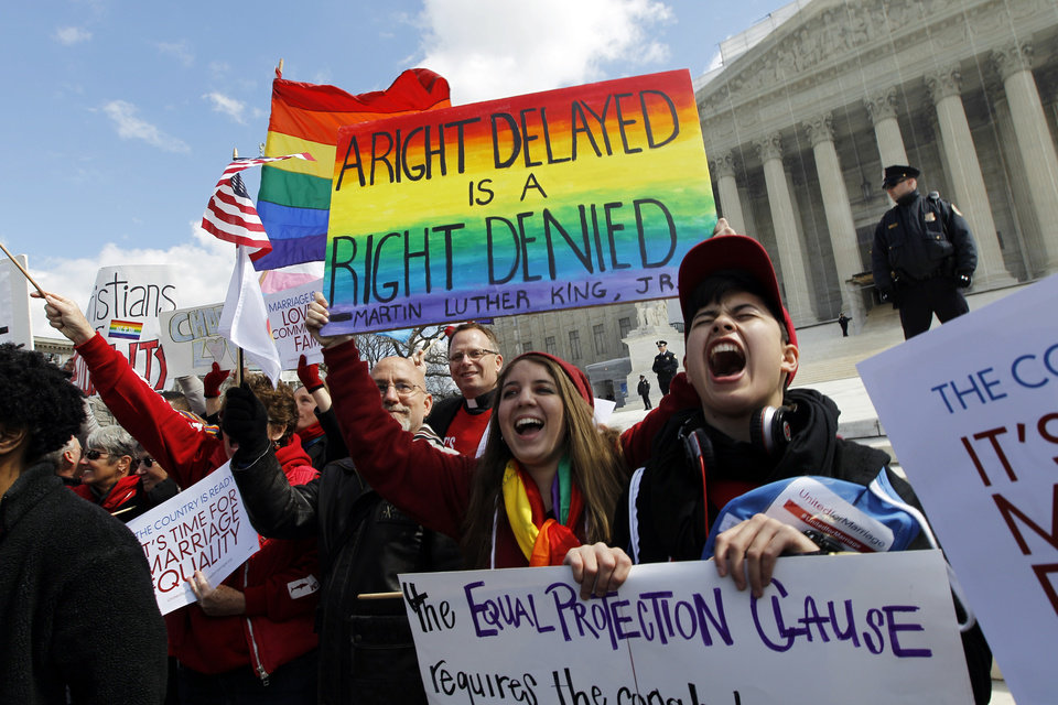 Photo - In this photo taken Wednesday, March 27, 2013, demonstrators holding flags chants in front of the Supreme Court in Washington. Ten years ago, same-sex marriage was legal nowhere in the United States. It's now allowed in nine states, with several more in the pipeline, yet many other states seem unlikely to follow suit unless forced to by Congress or the Supreme Court. It seems like a recipe for long-term conflict, but President Barack Obama and other Democratic Party leaders are now firmly ensconced in the ranks of gay-marriage supporters, and national opinion polls suggest that's now the prevailing view among the public. (AP Photo/Jose Luis Magana)