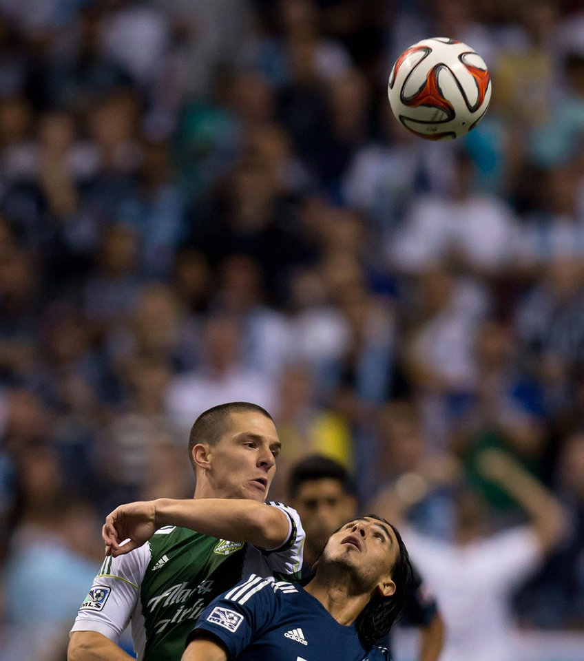 Photo - Portland Timbers' Will Johnson, left, watches Vancouver Whitecaps' Mauro Rosales, of Argentina, as he follows the ball during the first half of an MLS soccer game in Vancouver, British Columbia, on Saturday, Aug. 30, 2014. (AP Photo/The Canadian Press, Darryl Dyck)