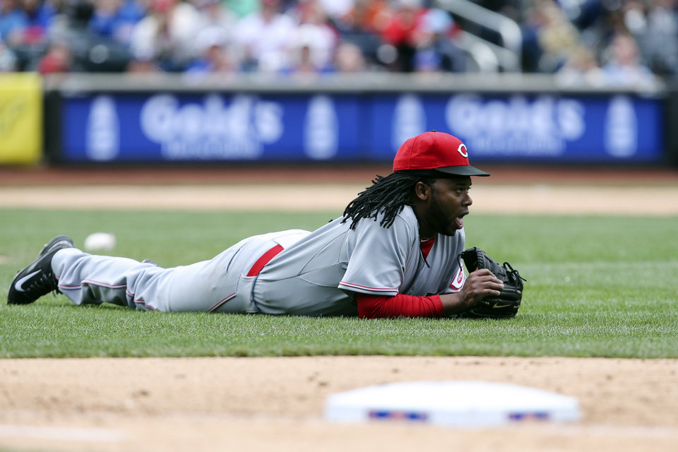 Photo - Cincinnati Reds starting pitcher Johnny Cueto lays on the field after diving for a ball in the seventh inning of a baseball game against the New York Mets at Citi Field, Saturday, April 5, 2014, in New York. (AP Photo/John Minchillo)