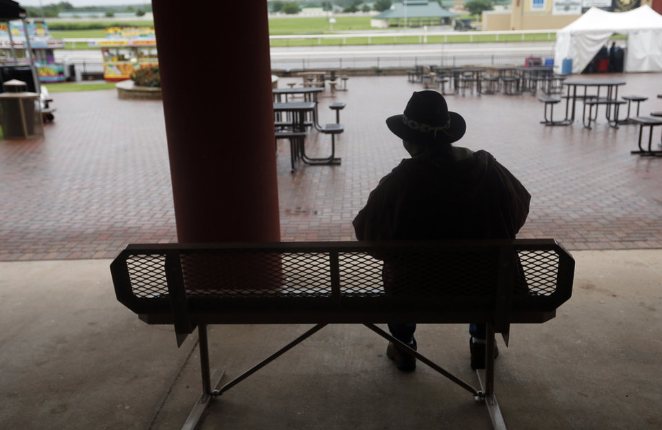 Photo - Dane Lena, of Phoenix, Ariz. waits out the rain on a covered bench during the 2014 Red Earth Festival at Remington Park on Friday, June 6, 2014 in Oklahoma City, Okla. This is the first year for the festival to be held at Remington Park. Photo by Chris Landsberger, The Oklahoman