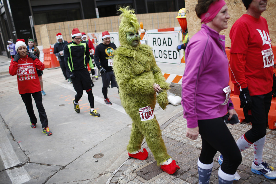 Melissa Howerton, who dressed up as the Grinch, walks away after finishing the SandRidge Santa Run in Oklahoma City, Saturday, Dec. 14, 2013.  Photo by Garett Fisbeck, For The Oklahoman
