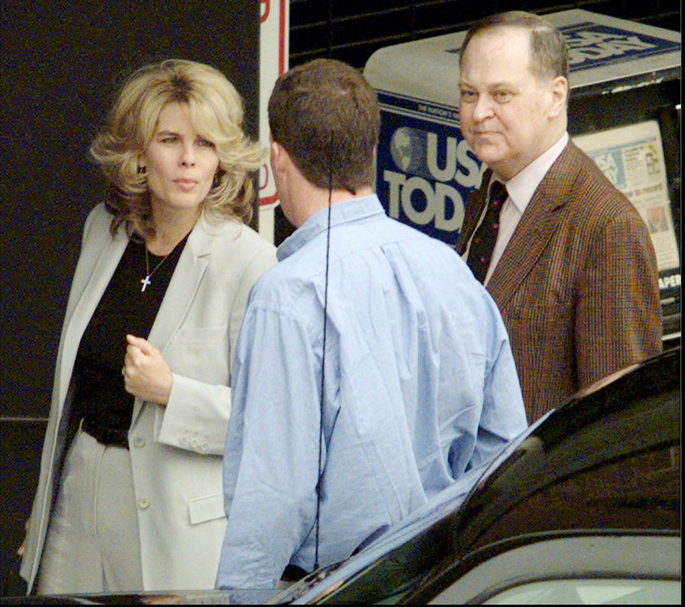Photo - This photo taken April 7, 1998 shows Frederick Koch, right, along with his sister-in-law Angela Koch, left, talking to the driver of their car before entering the federal courthouse in Topeka,  Kansas. The two were arriving for the second day of jury selection in the trial that has divided the Koch family in two. Bill and Frederick Koch are suing their brothers Charles and David for more than a  billion dollars. The Kochs are demonized by Democrats, who lack a liberal equal to counter their weight, and not entirely understood by Republicans, who benefit from their seemingly limitless donations.  (AP Photo/Travis Heying, The Wichita Eagle)