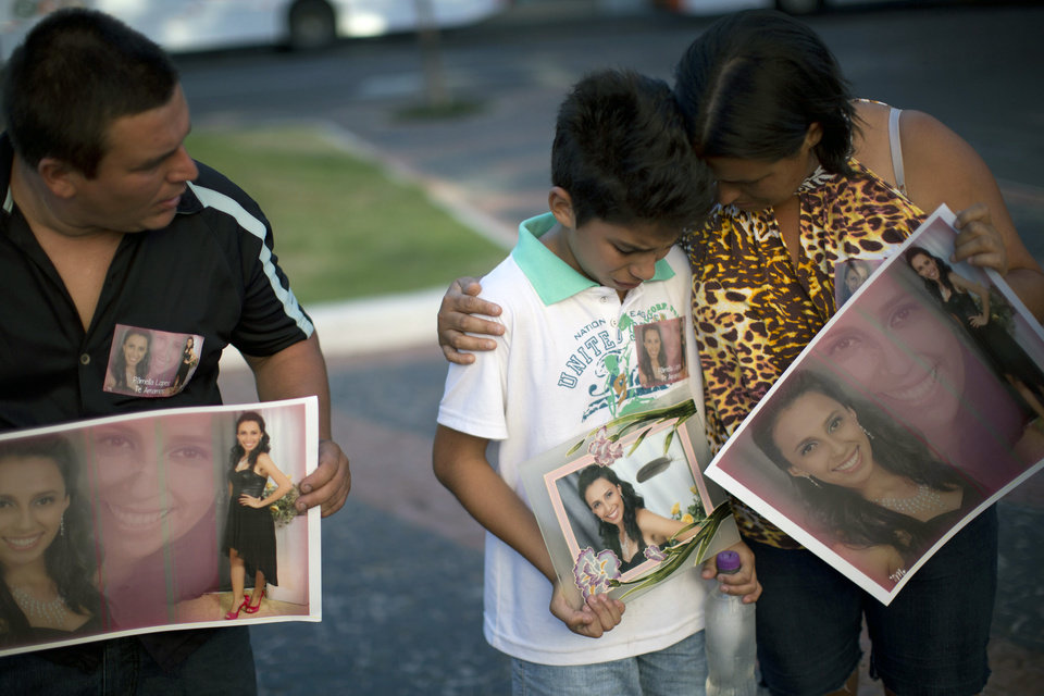 Relatives hold photographs of Pamella Lopes, who died in a nightclub fire, as they stand a public square near the nightclub in Santa Maria, Brazil, Monday, Jan. 28, 2013. A fast-moving fire roared through the crowded, windowless Kiss nightclub in this southern Brazilian city early Sunday, killing more than 230 people. Many of the victims were under 20 years old, including some minors. (AP Photo/Felipe Dana) ORG XMIT: XFD118