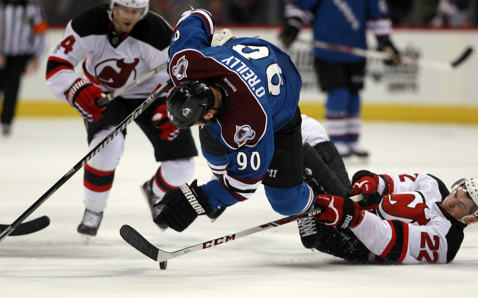 Photo - Colorado Avalanche center Ryan O'Reilly, center, is tripped by New Jersey Devils defenseman Adam Gelinas, right, as Devils center Adam Henrique covers in the second period of an NHL hockey game in Denver, Thursday, Jan. 16, 2014. (AP Photo/David Zalubowski)