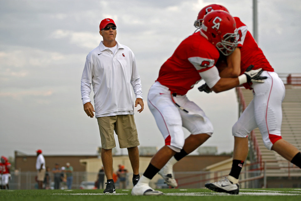 Carl Albert assistant coach Mike Corley runs players through drills before a high school football game between Carl Albert and Coweta in Midwest City, Friday, September 7, 2012.