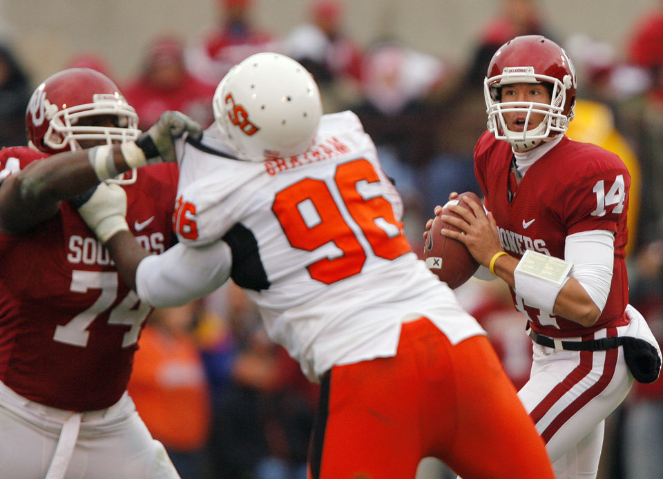 Photo - Oklahoma quarterback Sam Bradford (14) looks for an open man during the first half of the college football game between the University of Oklahoma Sooners (OU) and the Oklahoma State University Cowboys (OSU) at the Gaylord Family-Memorial Stadium on Saturday, Nov. 24, 2007, in Norman, Okla. 