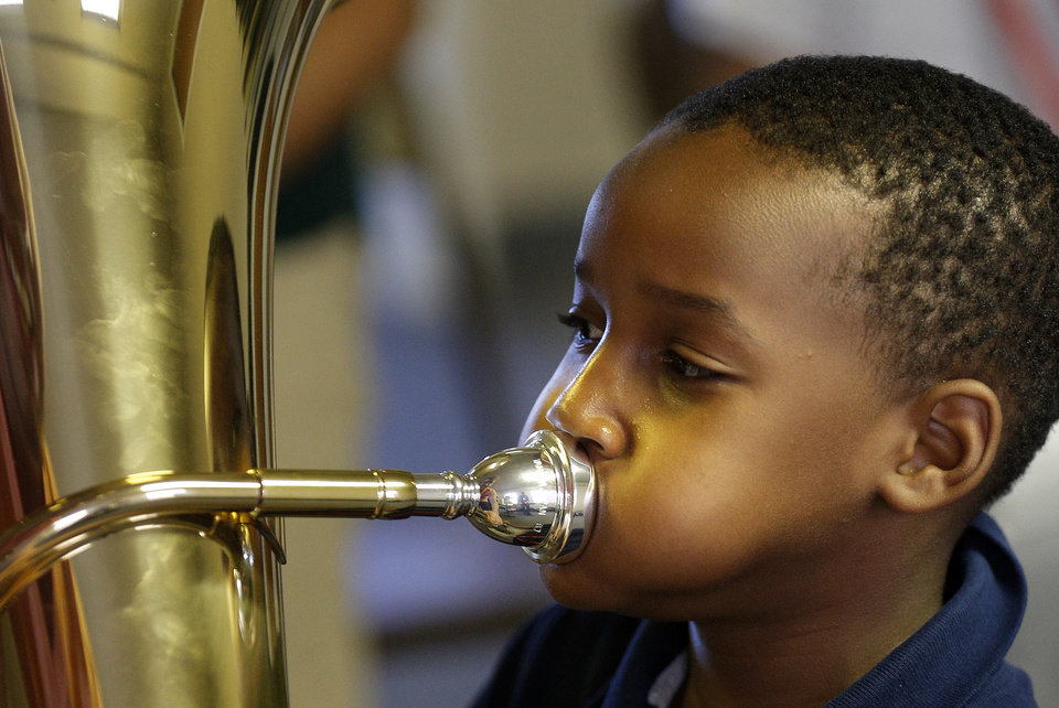 Photo - London Shepard blows into a tuba during a session of a new after-school music program called El Sistema Oklahoma under way at Trinity Baptist International Church, 1329 NW 23. The program is a partnership between St. Luke's United Methodist Church, Oklahoma City University and the Foundation for Oklahoma City Public Schools.   SARAH PHIPPS - SARAH PHIPPS