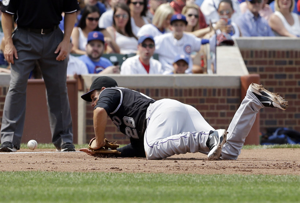 Photo - Colorado Rockies third baseman Nolan Arenado (28) can' t make the play on a single hit by Chicago Cubs' Arismendy Alcantara during the sixth inning of a baseball game in Chicago, Thursday, July 31, 2014. (AP Photo/Nam Y. Huh)