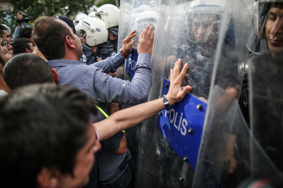 Photo - Riot police try to stop protesters who were  attacking the Soma offices of Prime Minister Recep Tayyip Erdogan's Justice and Development Party during his visit to the coal mine in Soma, Turkey, Wednesday, May 14, 2014. A violent protest erupted Wednesday in the Turkish city of Soma, where at least 238 coal miners have died after a mine explosion. Many in the crowd expressed anger at Prime Minister Recep Tayyip Erdogan's government. Rocks were being thrown and some people were shouting that Erdogan was a