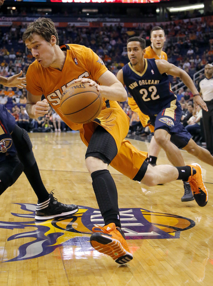 Photo - Phoenix Suns' Goran Dragic, of Slovenia, slips past New Orleans Pelicans' Brian Roberts during the second half of an NBA basketball game, Friday, Feb. 28, 2014, in Phoenix.(AP Photo/Matt York)