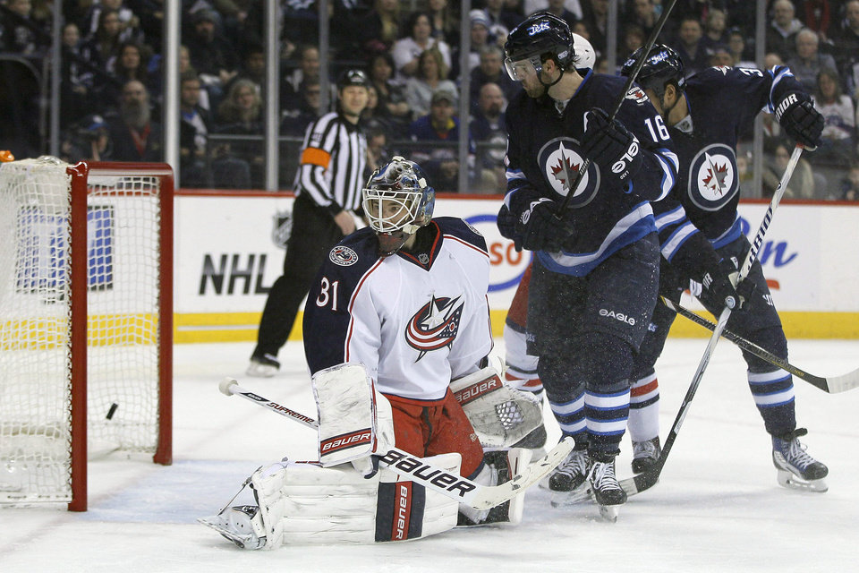 Photo - Columbus Blue Jackets goaltender Curtis McElhinney (31) and Winnipeg Jets' Andrew Ladd (16) watch as Jets' Tobias Enstrom's (39) shot from the point goes in during second period of an NHL hockey game in Winnipeg, Manitoba, on Saturday, Jan. 11, 2014. (AP Photo/The Canadian Press, John Woods)