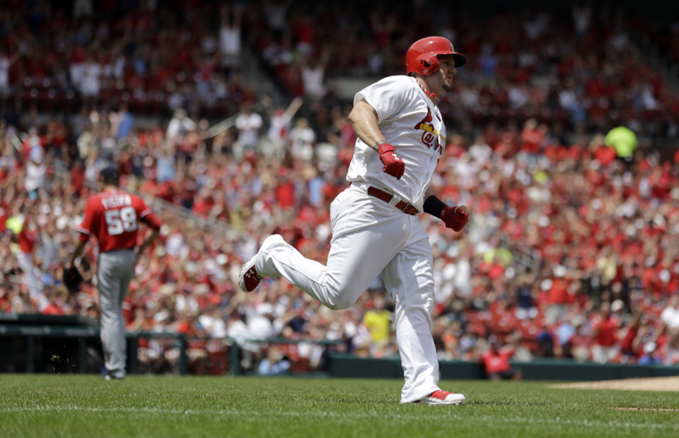 Photo - St. Louis Cardinals' Matt Adams, right, rounds the bases after hitting a two-run home run off Washington Nationals starting pitcher Doug Fister, left, during the second inning of a baseball game on Sunday, June 15, 2014, in St. Louis. (AP Photo/Jeff Roberson)