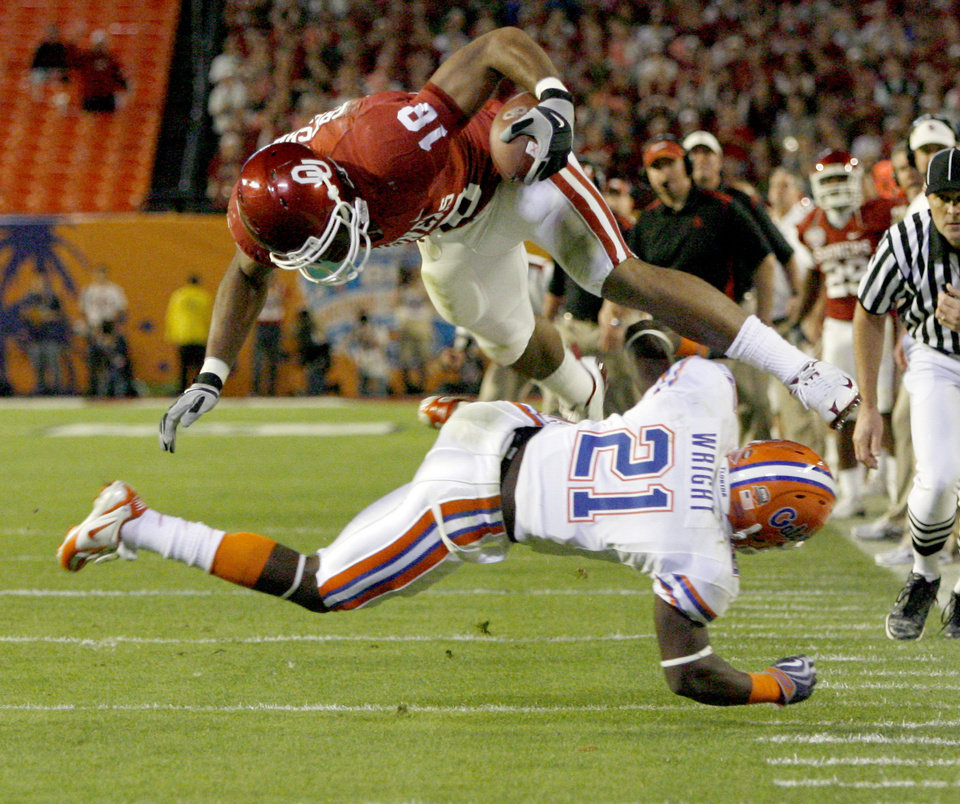 Photo - OU's Jermaine Gresham leaps over Florida's Major Wright during the first half of the BCS National Championship college football game between the University of Oklahoma Sooners (OU) and the University of Florida Gators (UF) on Thursday, Jan. 8, 2009, at Dolphin Stadium in Miami Gardens, Fla. PHOTO BY BRYAN TERRY, THE OKLAHOMAN