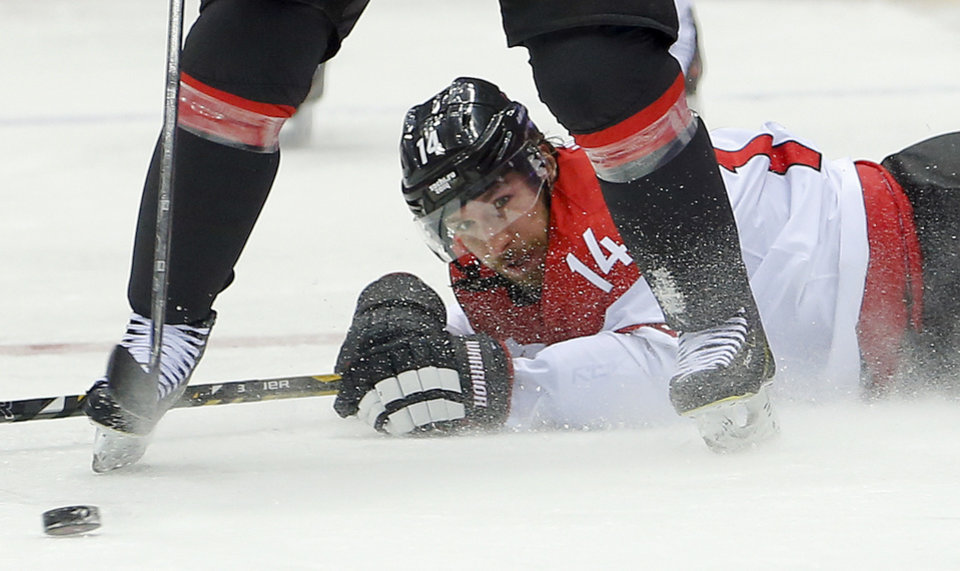 Photo - Austria forward Andreas Nodl hits the ice against Canada in the second period of a men's ice hockey game at the 2014 Winter Olympics, Friday, Feb. 14, 2014, in Sochi, Russia. (AP Photo/Mark Humphrey)