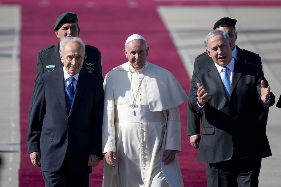 Photo - Pope Francis, center, walks with Israeli President Shimon Peres, left, and Prime Minister Benjamin Netanyahu, right, during an  official arrival ceremony at Ben Gurion airport near Tel Aviv, Israel, Sunday, May 25, 2014. May 25, 2014. Pope Francis took a dramatic plunge Sunday into Mideast politics while on his Holy Land pilgrimage, receiving an acceptance from the Israeli and Palestinian presidents to visit him at the Vatican next month to discuss embattled peace efforts. The summit was an important moral victory for the pope, who is named after the peace-loving Francis of Assisi. Israeli-Palestinian peace talks broke down in late April, and there have been no public high-level meetings for a year. (AP Photo/Oded Balilty)