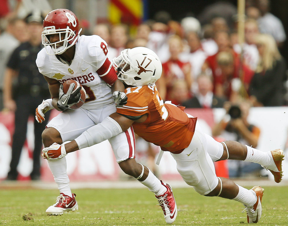 Photo - UT's Adrian Phillips (17) stops OU's Jalen Saunders (8) in the first half during the Red River Rivalry college football game between the University of Oklahoma Sooners and the University of Texas Longhorns at the Cotton Bowl Stadium in Dallas, Saturday, Oct. 12, 2013. Photo by Nate Billings, The Oklahoman