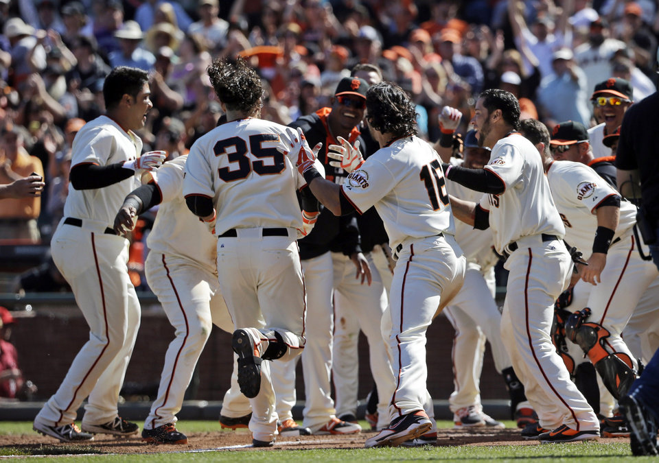 Photo - San Francisco Giants' Brandon Crawford (35) is greeted at the plate after his walk-off home run to beat the Colorado Rockies during the 10th inning of a baseball game on Sunday, April 13, 2014, in San Francisco. San Francisco won 5-4. (AP Photo/Marcio Jose Sanchez)