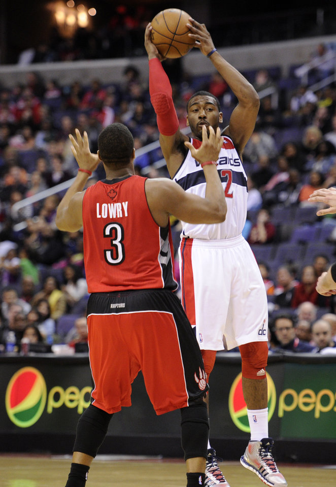 Photo - Washington Wizards guard John Wall (2) looks to pass against Toronto Raptors guard Kyle Lowry (3) during the second half of an NBA basketball game, Sunday, March 31, 2013, in Washington. The Wizards won 109-92. (AP Photo/Nick Wass)