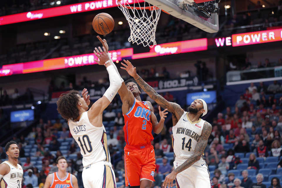 Photo - Oklahoma City Thunder guard Shai Gilgeous-Alexander (2) goes to the basket between New Orleans Pelicans center Jaxson Hayes (10) and forward Brandon Ingram (14) in the first half of an NBA basketball game in New Orleans, Sunday, Dec. 1, 2019. (AP Photo/Gerald Herbert)