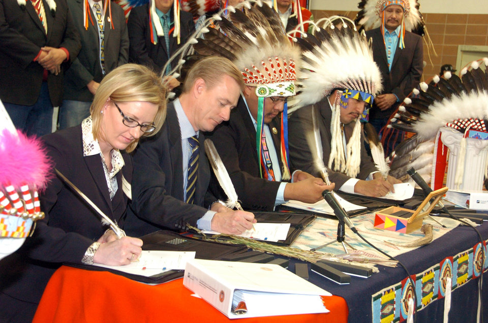 Representatives of Cloud Peak Energy and Montana\'s Crow Tribe sign an agreement Thursday Jan. 24, 2013, that gives the mining company leasing options on 1.4 billion tons of coal beneath the Crow Indian Reservation, in Billings, Mont. Pictured from left are Cloud Peak legal counsel Amy Stefonick, company chief executive Colin Marshall, Crow Tribal Chairman Darrin Old Coyote and Tribal Executive Secretary Alvin Not Afraid. The deal would expand mining on the reservation with the coal likely to be exported overseas. (AP Photo/Matthew Brown)
