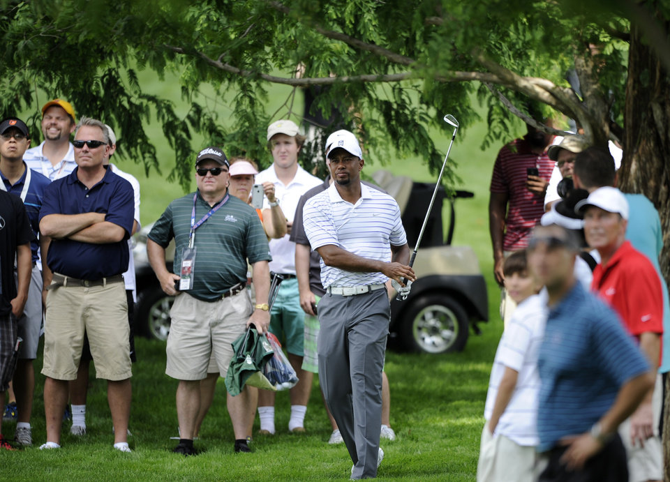 Photo - Tiger Woods watches his shot from the rough on the sixth hole during the Pro-Am at the Quicken Loans National golf tournament, Wednesday, June 25, 2014, in Bethesda, Md. (AP Photo/Nick Wass)