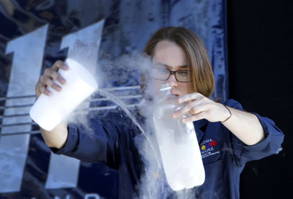 Photo - Trevor Taylor, with The Science Museum of Oklahoma, pores liquid nitrogen into a plastic bottle to make it explode during a show at the OPUBCO Pavilion at the Oklahoma State Fair, Tuesday, September 18, 2012. Photo By David McDaniel/The Oklahoman