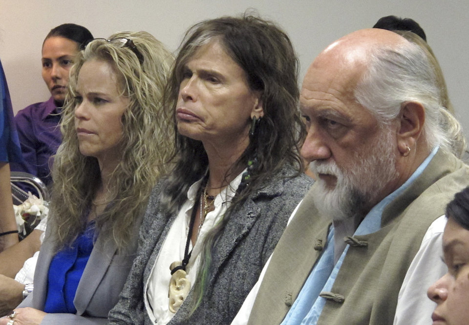 Aerosmith lead singer Steven Tyler, center, sits with his attorney Dina LaPolt, left, and Fleetwood Mac drummer Mick Fleetwood as they listen to testimony on a celebrity privacy bill during a hearing at the Hawaii Capitol in Honolulu on Friday, Feb. 8, 2013. Rock legends StevenTyler and Mick Fleetwood convinced a Hawaii Senate committee on Friday to approve a bill to protect celebrities or anyone else from intrusive paparazzi. The state Senate Judiciary Committee approved the so-called StevenTyler Act after the stars testified. The bill would give people power to sue others who take photos or video of their private lives in an offensive way. (AP Photo/Oskar Garcia)