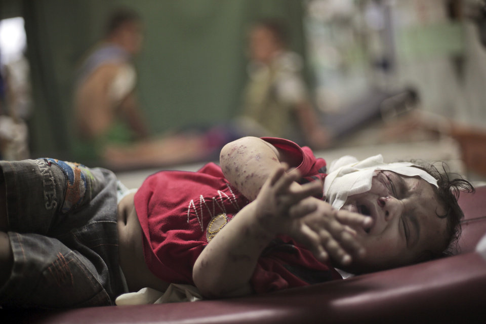 Photo - A Palestinian boy cries while receiving treatment for injuries caused by an Israeli strike at a U.N. school in Jebaliya refugee camp, at the Kamal Adwan hospital in Beit Lahiya, northern Gaza Strip, Wednesday, July 30, 2014. Several Israeli tank shells slammed into the crowded U.N. school used as shelter for refugees in the Gaza war early on Wednesday. (AP Photo/Khalil Hamra)