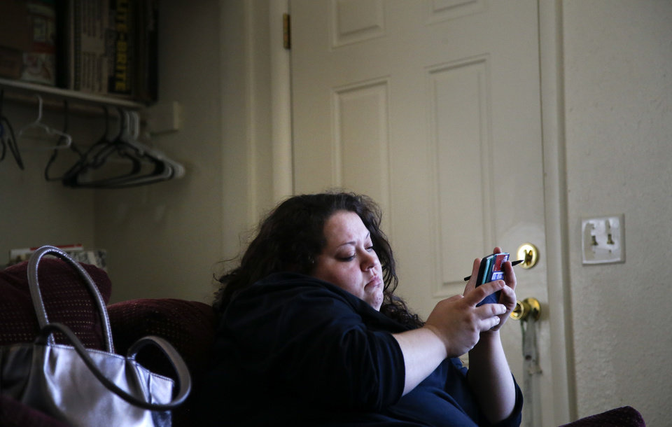 Photo -  Desha Bailey texts March 17 as she rests on the couch after a 10-hour shift at Whirlpool in Tulsa. Desha is in recovery for drug addiction and was able to regain custody of her two sons, find a stable job and purchase a home in Tulsa. [Photo by Jessie Wardarski, Tulsa World]