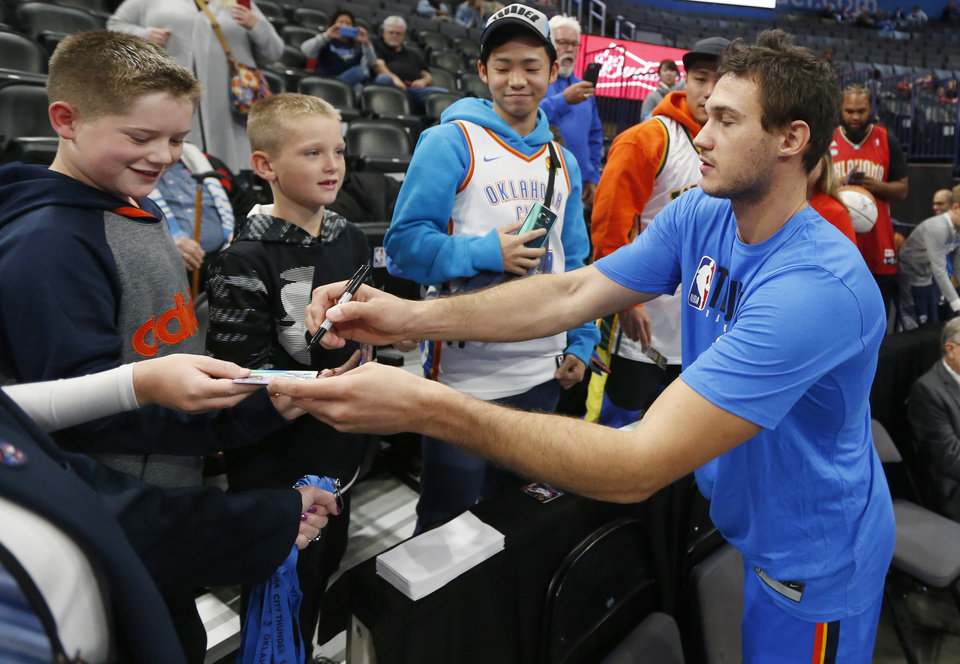 Photo - Oklahoma City's Danilo Gallinari (8) signs autographs after warming up before an NBA basketball game between the Oklahoma City Thunder and the Washington Wizards at Chesapeake Energy Arena in Oklahoma City, Friday, Oct. 25, 2019. [Nate Billings/The Oklahoman]