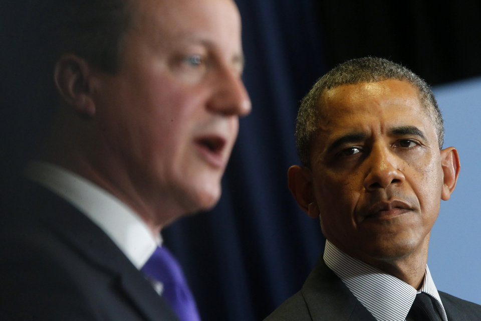 Photo - President Barack Obama listens as British Prime Minister David Cameron speaks during a news conference at the G7 summit in Brussels, Belgium, Thursday, June 5, 2014. (AP Photo/Charles Dharapak)