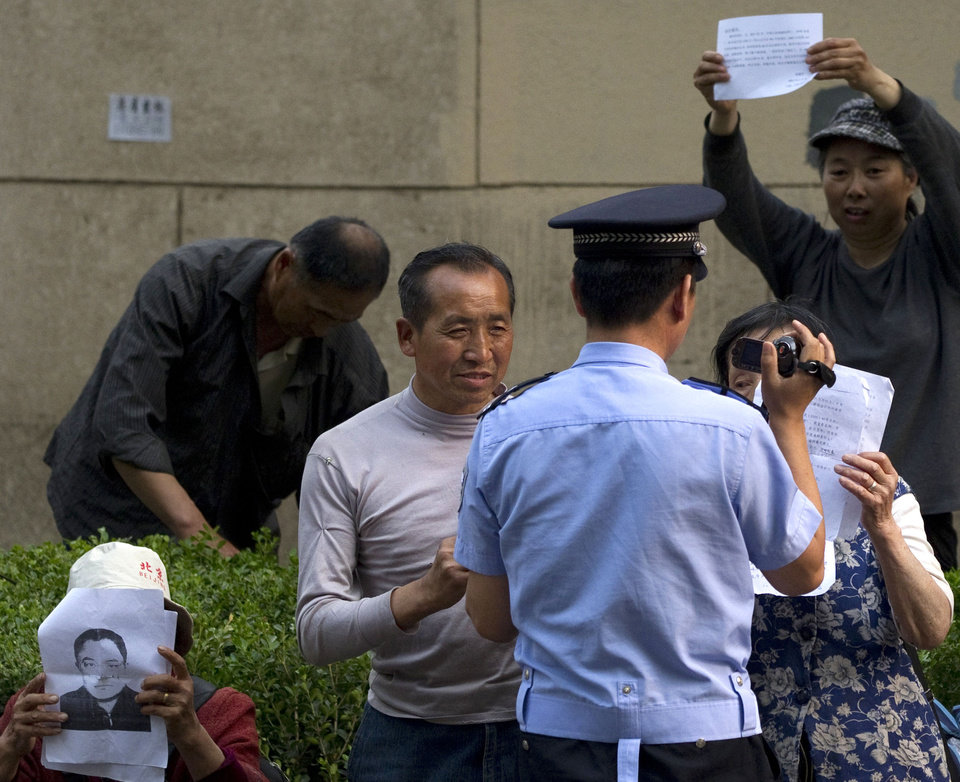 Photo -   A policeman takes a video of petitioners who hold up papers to attractions for their cases outside the hospital where blind activist Chen Guangcheng is staying for treatment in Beijing Monday, May 7, 2012. The Chinese activist who triggered a diplomatic dispute between China and the United States said Monday he was confident that Beijing would hold up its end of a tentative deal to let him study overseas. (AP Photo/Alexander F. Yuan)