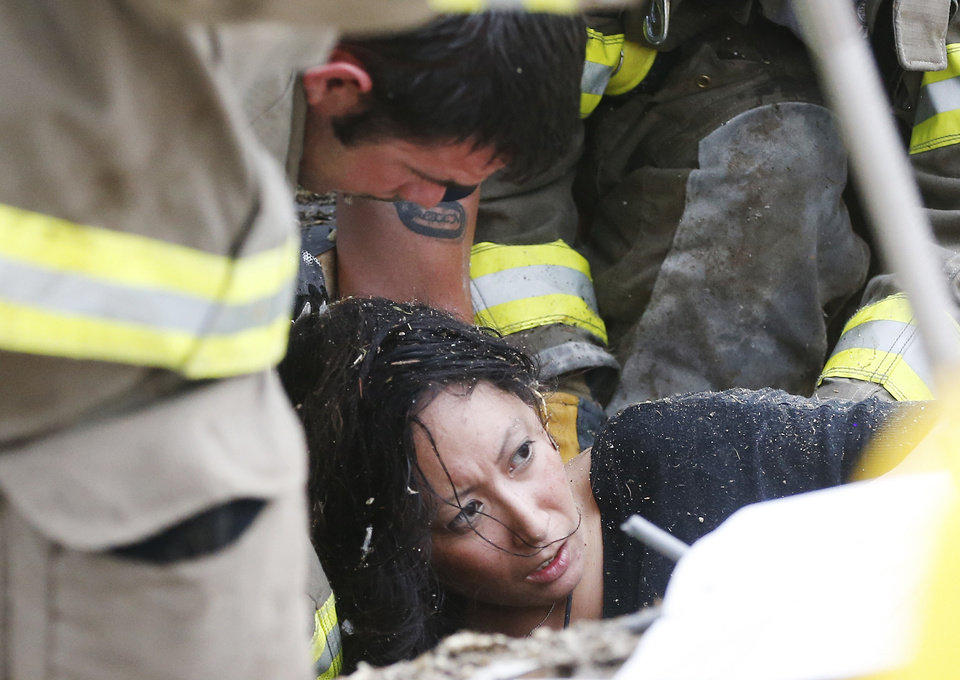 A woman is pulled out from under tornado debris at the Plaza Towers School in Moore, Okla., Monday, May 20, 2013. A tornado as much as a mile (1.6 kilometers) wide with winds up to 200 mph (320 kph) roared through the Oklahoma City suburbs Monday, flattening entire neighborhoods, setting buildings on fire and landing a direct blow on an elementary school.(AP Photo Sue Ogrocki) ORG XMIT: OKSO116