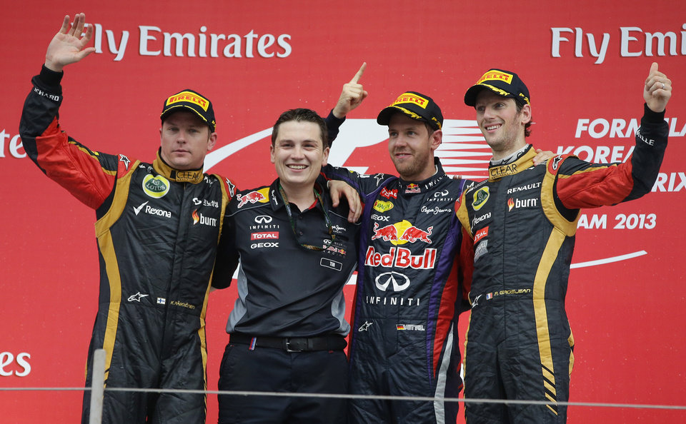 Race winner Red Bull driver Sebastian Vettel, second right, of Germany celebrates with Tim Malyon, second left, performance engineer for Red Bull Racing and second placed Lotus driver Kimi Raikkonen, left, of Finland and third placed Lotus driver Romain Grosjean, right, of France on the podium after the Korean Formula One Grand Prix at the Korean International Circuit in Yeongam, South Korea, Sunday, Oct. 6, 2013. (AP Photo/Aaron Favila)