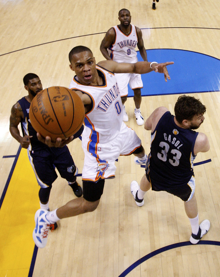 Photo - Oklahoma City Thunder guard Russell Westbrook shoots between Memphis Grizzlies guard O.J. Mayo, left, and center Marc Gasol, right, of Spain, in the first half of Game 7 of a second-round NBA basketball playoff series in Oklahoma City, Sunday, May 15, 2011. Oklahoma City won 105-90. (AP Photo/Sue Ogrocki)