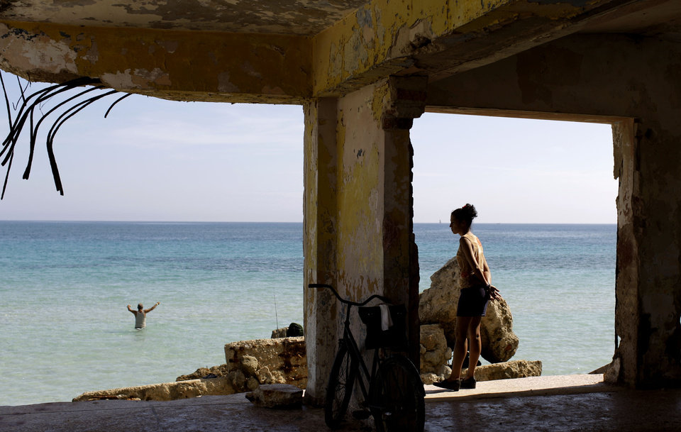 Photo - In this May 23, 2013 photo, a woman stands in what remains of a destroyed school as she watches a fisherman on the shores of Havana, Cuba. With its coastal towns and cities, the Caribbean is one of the most vulnerable regions to a changing climate. Hundreds of villages are threatened by rising seas, and more frequent and stronger hurricanes have devastated agriculture in Haiti and elsewhere. (AP Photo/Franklin Reyes)