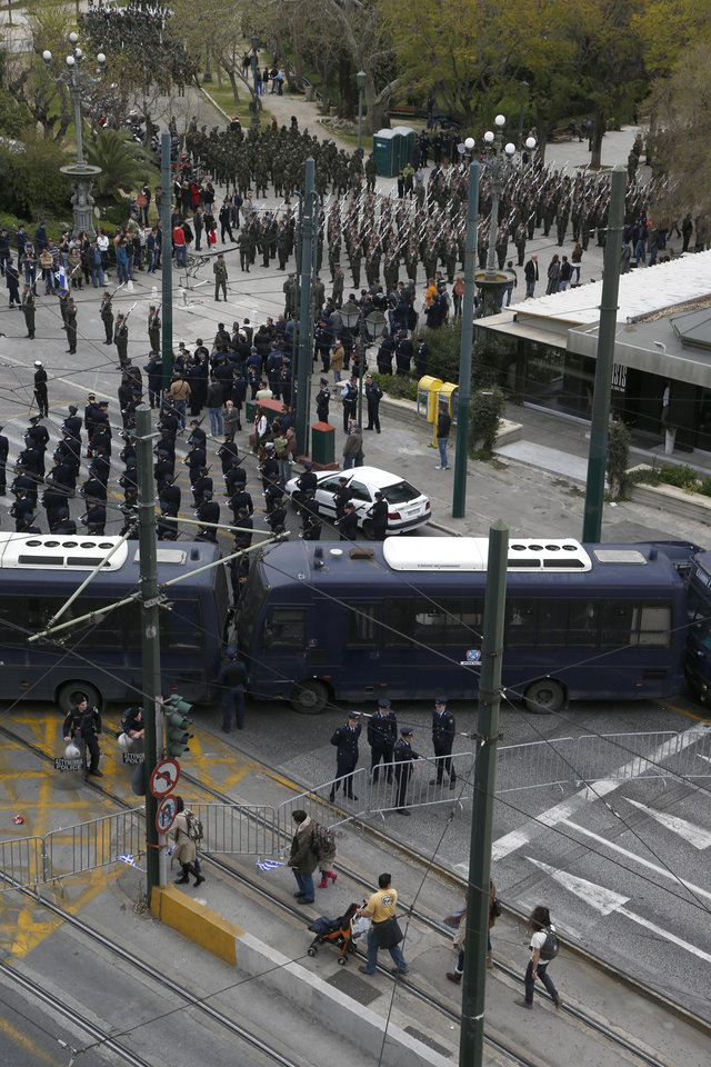 Police buses and metal barriers keep people from getting close to the military parade for the Independence Day in central Athens, Monday March 25, 2013. For the second straight year, heavy police presence, for fear of disruptive incidents, has effectively closed off central Athens, not only for vehicles, but also for people who, in the past, lined up the parade route. (AP Photo/Dimitri Messinis)